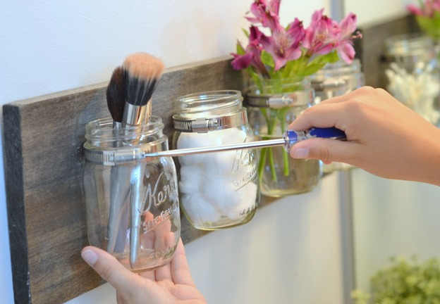 Unscrewing a mason jar from a bathroom storage