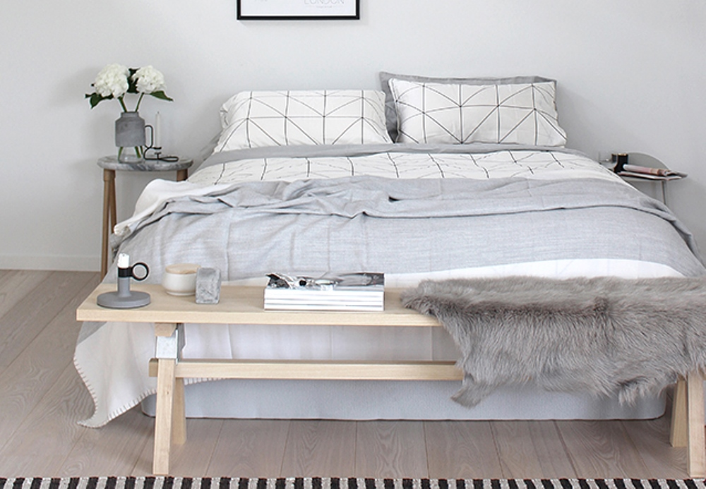 A wooden bench in front of a bed