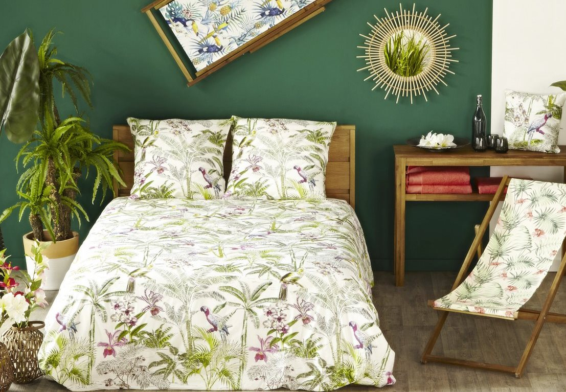 Jungle style with flowered bed linen and a sun mirror