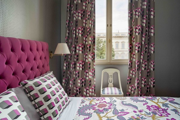Hotel room with pink curtain, cushions and bed linen