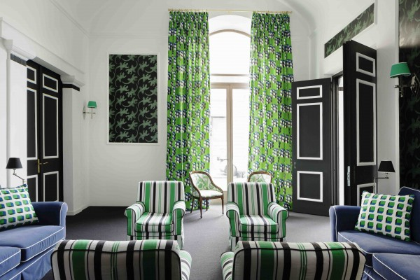 Hotel room with green coloured curtains and cushions