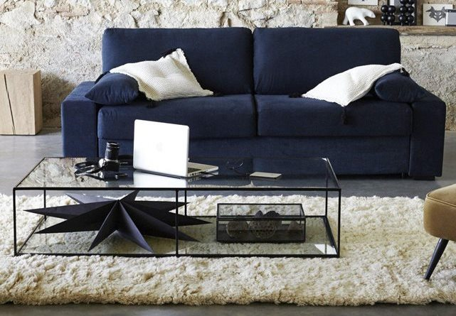 blue couch with a white rug