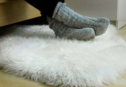 Foot with socks on a sheepskin