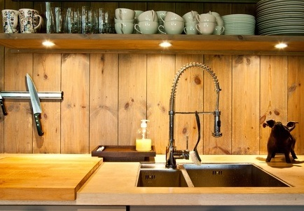 Kitchen area with sink, three lights and a shelf with tea cups