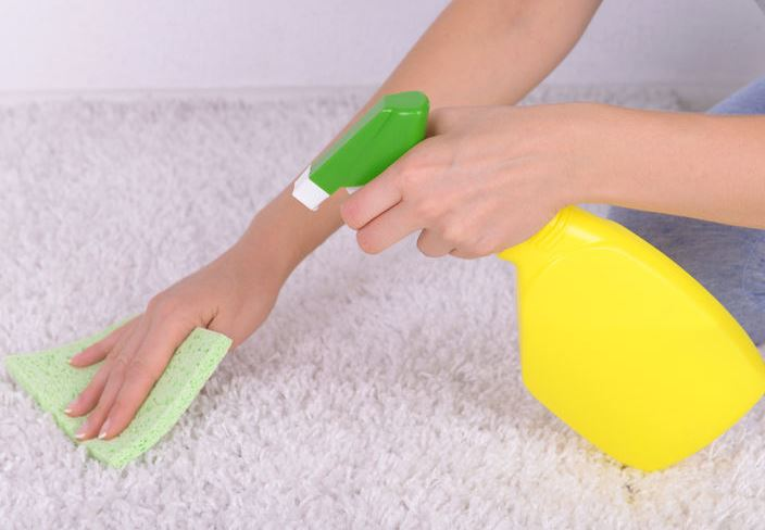 Woman's hand cleaning a white carpet with a spray bottle
