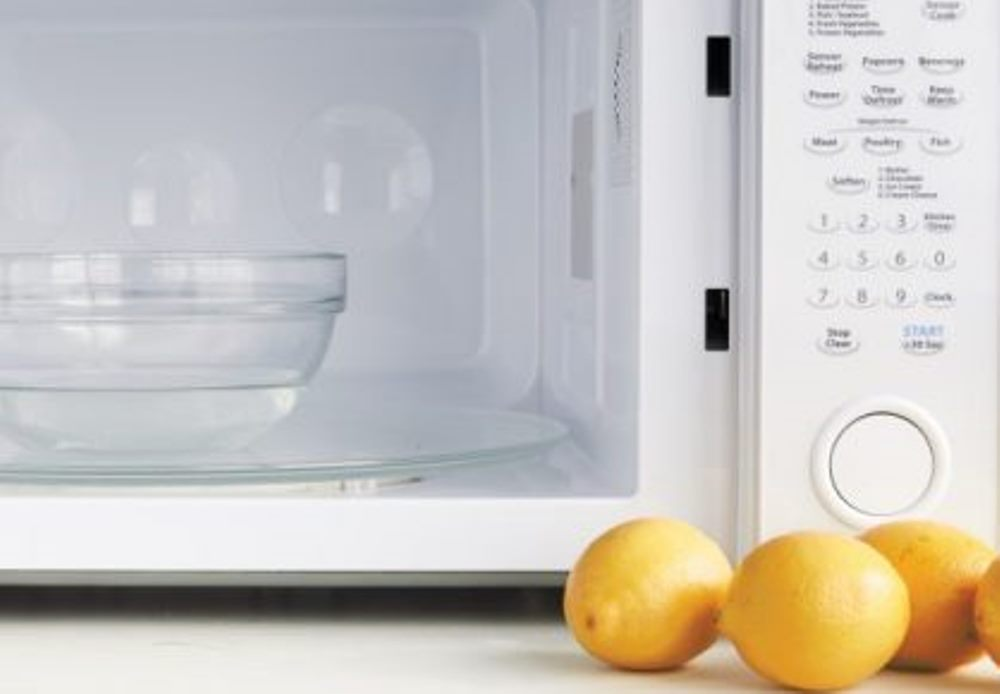 Lemon and bowl of water close to a microwave