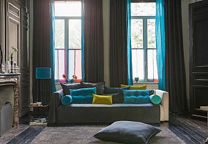 Dark living room with colored curtains and cushions